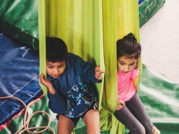 Niña y niño sentados en una hamaca de tela
