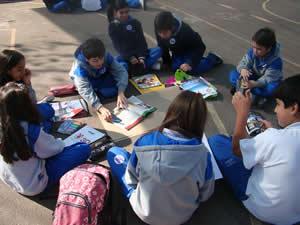 Escolares sentados en el suelo, estudiando