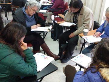 Adultos leyendo, sentados en círculo en una sala de clases