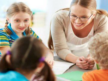 Profesora y niños sonriendo, apoyados sobre una mesa de colegio