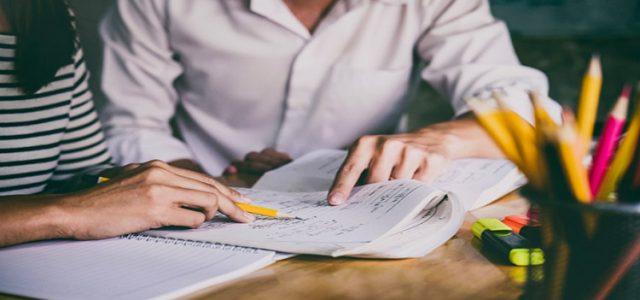 Dos personas estudiando con un cuaderno