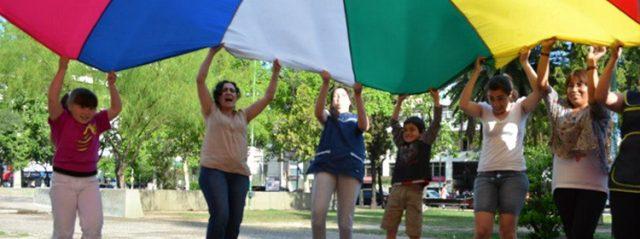 Adolescentes y adultos alzando un toldo de colores, al aire libre