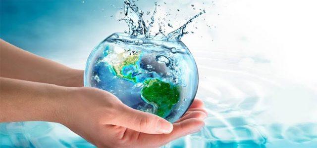 Manos tomando una pecera con forma de planeta Tierra, salpicando agua