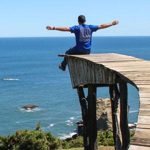 Hombre sentado frente al mar con los brazos abiertos