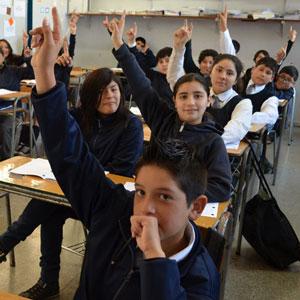 Niños levantando la mano en una sala de clases