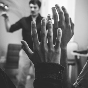 Adultos levantando la mano en una sala de clases