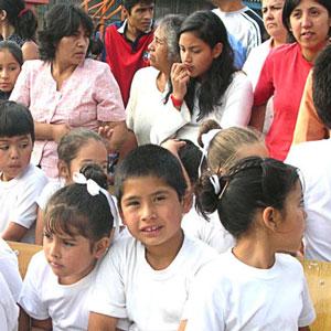 Grupo de niños y apoderados sentados en el patio de un colegio