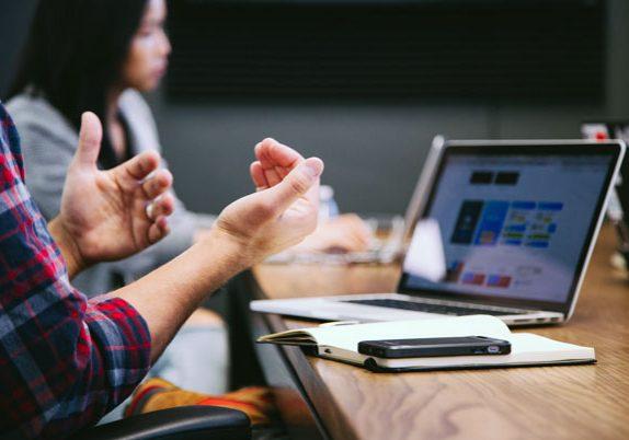 Personas conversando en un escritorio de trabajo