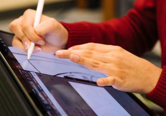 Persona dibujando sobre la pantalla de un computador